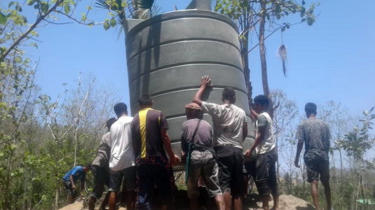 Community members position a water tank in Bobonaro, Timor-Leste
