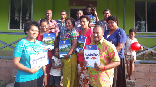 Training group participants in Fiji holding up their training booklets