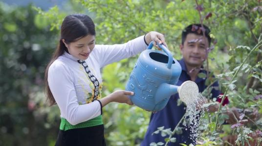 Tuoi watering her garden